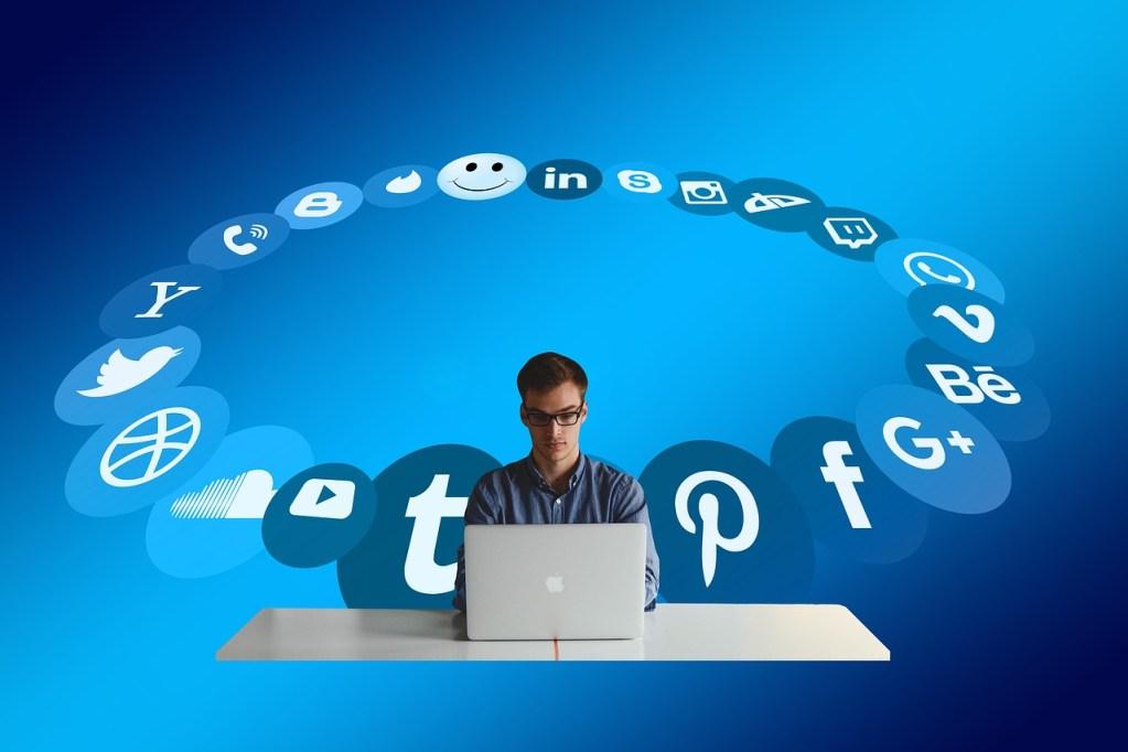 persona usando computadora rodeada de logotipos de redes sociales, emulando ser un social media manager o un community manager, para artículo en que se comparan ambos puestos