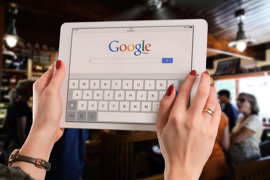 página principal de google search mostrada en una tablet sostenida por las manos de una persona