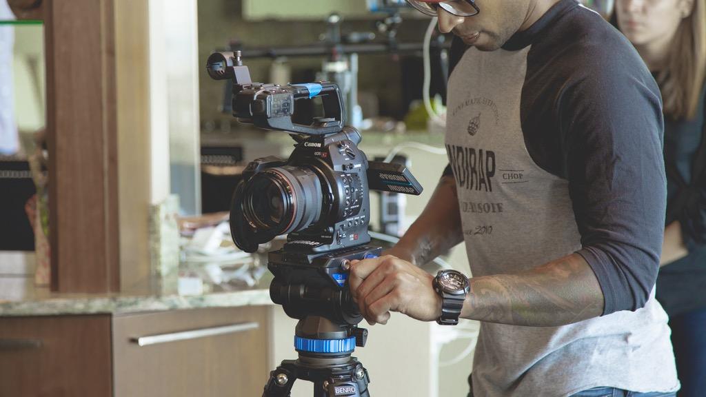 persona grabando video con cámara, ilustrando artículo sobre ganancias de youtubers