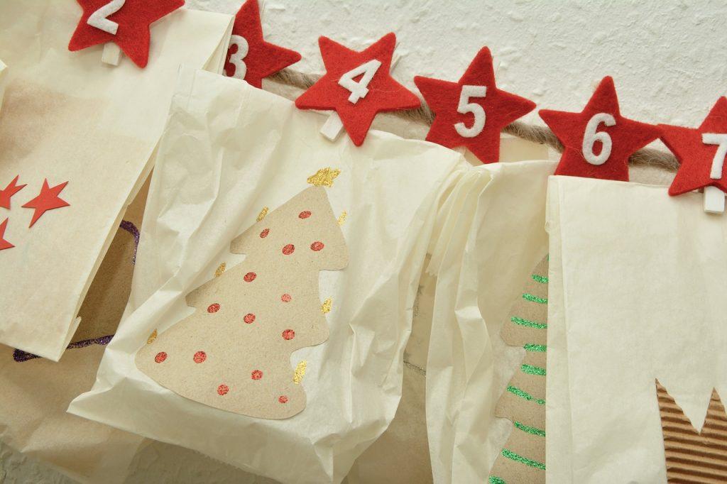 calendario de adviento mostrando días 2 al 7 en estrellas rojas sosteniendo bolsas con diseños de árboles navideños, para ilustrar que para el marketing en facebook las fechas decembrinas van más allá del 24 de diciembre