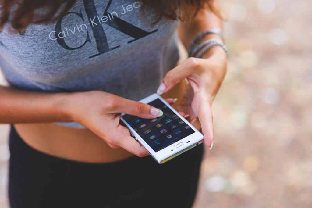 chica utilizando un smartphone, en las campañas de marketing en facebook es muy importante enfocarse en los dispositivos móviles