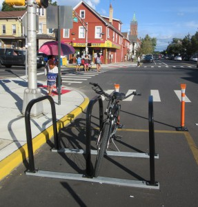 A bicycle corral adjacent to an intersection helps drivers see pedestrians crossing the street.