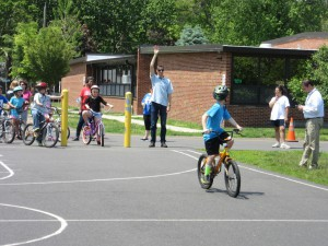 KMM representative Peter Bilton raises his hand so that students can practice looking backwards while riding in a straight line