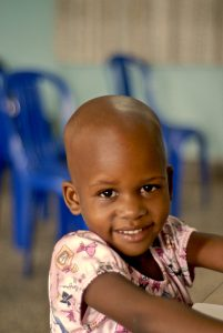 a smiling child who has been treated for hydrocephalus
