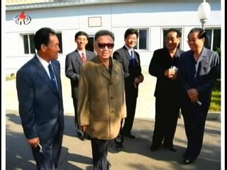 Kim Hong-jun, Factory Director of the Pyongyang Textile Machine Factory, with Kim Jong-il.  KWP Financial Planning Director Pak Nam-gi and KWP Administration Director Jang Song-thaek grinning at the far right (Photo: Korea Central TV)
