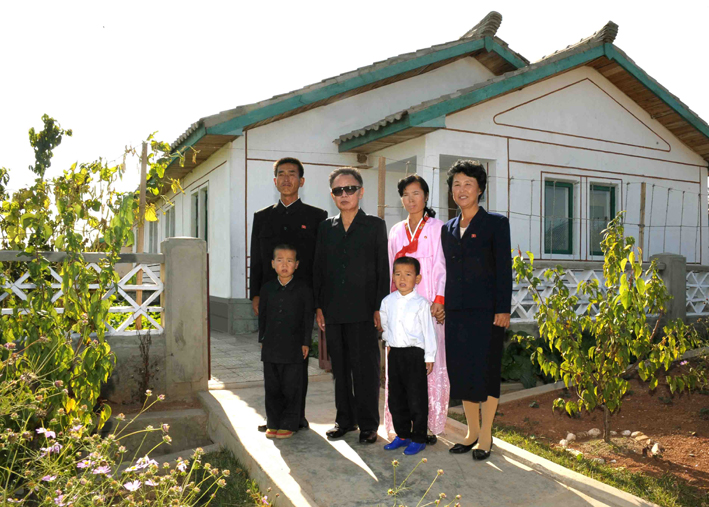 Kim Jong-il posing with the family of former KPA officer Ri Yong-jun at Migok Cooperative Farm (Photo: Korean Central News Agency)