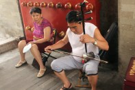 Mand spiller på en Erhu, mens konen får sig en slapper.
