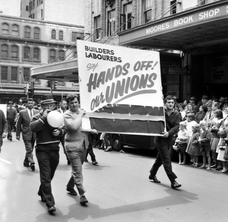 # McQuillan, Ern, 1926- # Member of the Builders Labourers Union carrying a banner on the 6 Hour March, Sydney, 6 October 1964