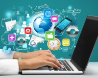 symbols representing different types of medical information hover over a laptop on which a doctor types