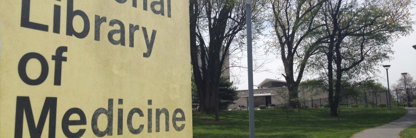 "Close-up of sign reading ""National Library of Medicine,"" with the library building visible in the background"