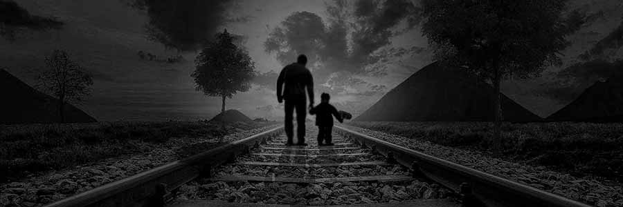 Silhouette of a man and child holding hands as they walk away from the camera along a receding set of railroad tracks