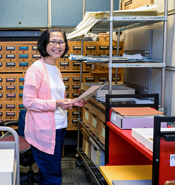 NLM employee in front of old library card catalog.