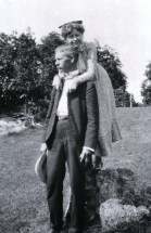 Standing by rock, with his daughter Blossom - arms around his neck.