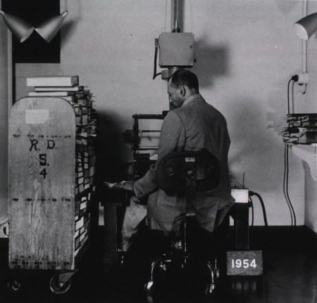 A man is seated at microfilm camera with truck of publications nearby.