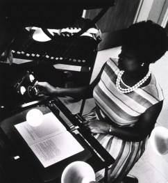 A woman adjusts a camera while photographing a book on a copystand under bright lights.