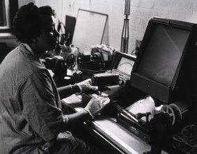 A woman in a smock and white cotten gloves reviews a film strip with an instrument.