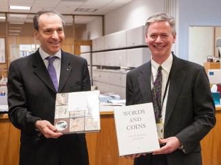 Michael North and the Greek Ambassador exchange gift books.