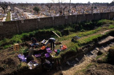 Young people work in a trench in a cemetary.