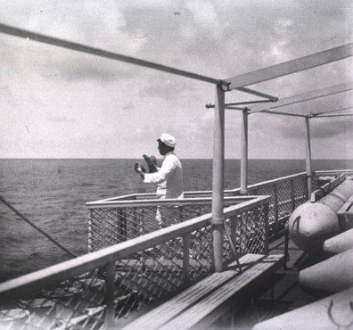 A sailor on shipboard holds birds in his hands.