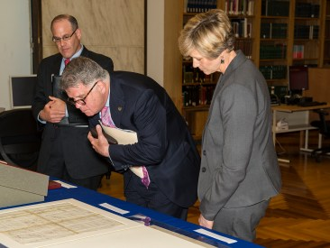 Three people look at archival collection materials on display.