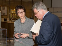 A woman speaks to a man who is holding a folder, looking into a display case.