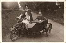 Two White female nurses in a motorcycle with sidecar. Both wear white uniforms under their cloaks.