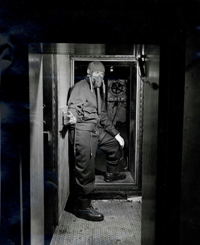 A man in a breathing mask stands in the doorway of an airtight chamber.
