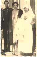 A man in uniform and a well dressed woman stand with a nurse holding an infant.