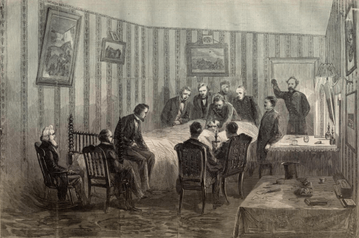 An engraving of a wallpapered room in which people stand and sit around the bed where the President lays.