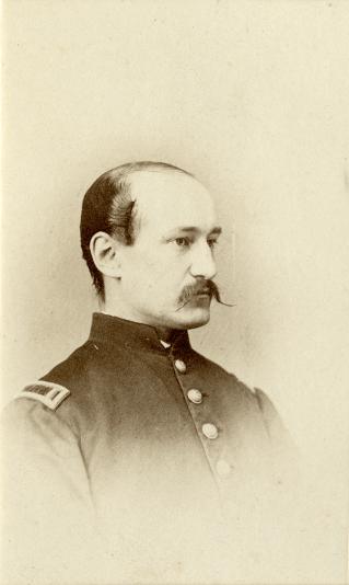 Vignette bust portrait of a young man in a mustache and uniform.