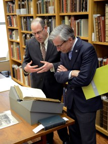 Two men talk while looking at a book.