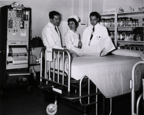 Interior view, opening of trauma center, two doctors and a nurse stand by a hospital bed surrounded by medical equipment.