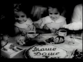 Two girls sit at a party table with a cake.