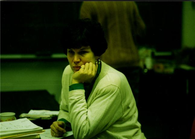 A candid photograph of Jaquelyn Campbell seated at a table with papers.