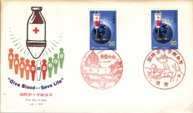 1974 First Day of Issue stamps on a card asking for blood donations. The stamps feature a bottle of blood with a red cross symbol on them superimposed over an image of the world. On the card is an image of a bottle of blood with a red cross on it hovering over 10 human figures, each representing a blood type.