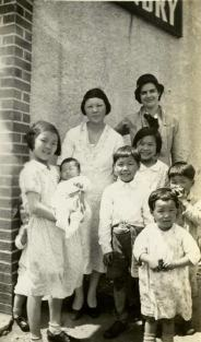 A family with 7 children pose in a doorway.