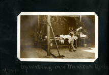 Three men in aprons work on a person lying on a table under a leafy arbor as a child walks by.