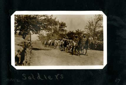 A rough line of men in uniform on horseback, with a flag, riding down a road.
