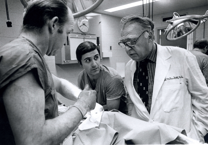 Ravitch oversees the work of two men in an operating training room.