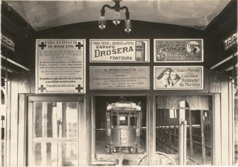 Photograph of posters hanging inside a streetcar.