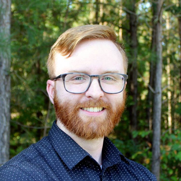 Photo of Nick Vogel smiling. He has auburn red hair, wears thick, plastic framed glasses, and has a full beard. There is a forest in the background.