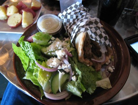 A traditional Greek gyro with a Greek salad and potatoes