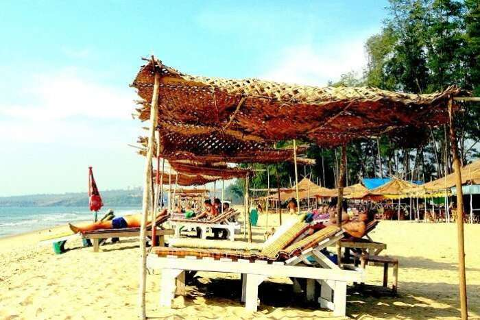 Tourists relax at the recliners and boat shacks at Querim Beach