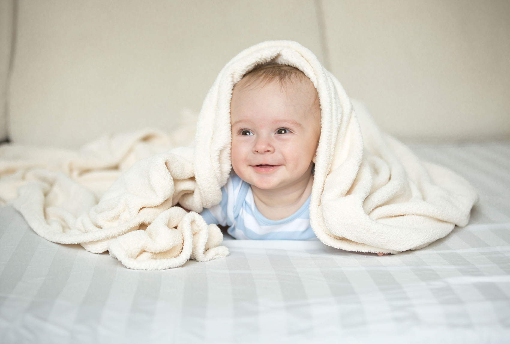 Baby playing under a blanket