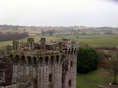 The ornate Tudor towers of Raglan Castle, backed by damp Welsh hills.