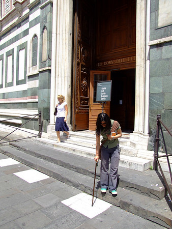My partner, because he is cruel and horrible, finds this picture hilarious.  Me, exiting the duomo, with walking stick.  photo by my partner, naturally