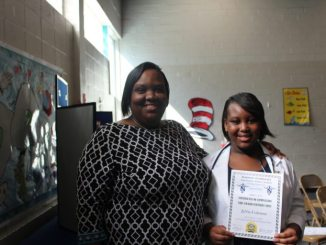 Lakecia Coleman (left) stands with her daughter Ja'Nia, 11, after receiving her certificate for completing the nursing program at Robinson Elementary School. (Ariel Worthy/The Birmingham Times)