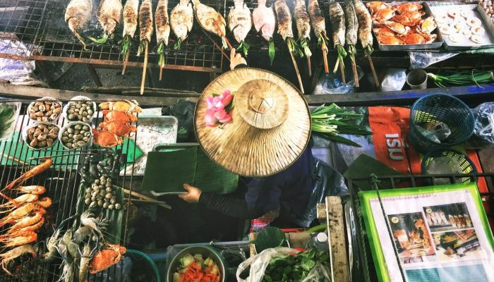 person wearing rice hat cooking in Thai market