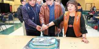 Jordan Peterson, vice-president of the Gwich'in Tribal Council, left, cuts the cake with Willard Hagen, former president of GTC, and Bobbie Jo Greenland-Morgan, current president of GTC. - Stewart Burnett/NNSL photo