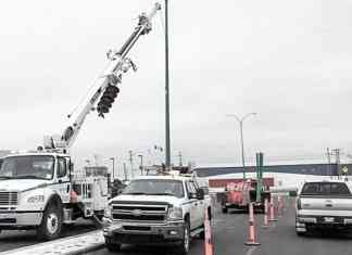 Northland Utilities crews work to replace streetlights along a median on Franklin Avenue. Re-lighting the street is one of the final steps of a two year construction project. James O'Connor/NNSL photo